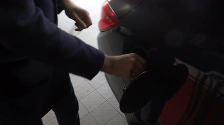 cúbico : Man refueling car, twisting cover of fuel tank and leaving gasoline station