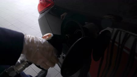 filling station : Respectably dressed man drives up to gas station to refuel his car, self service
