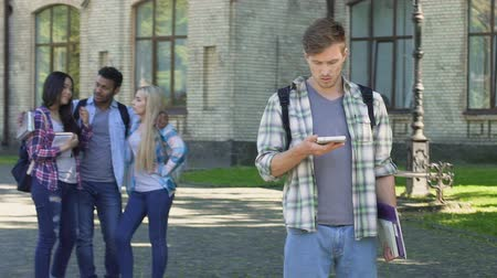 smutek : Sad male student scrolling on cellphone, Hispanic man flirting with females