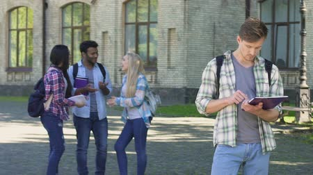 ethic : Nerd male standing alone and reading essay, group of multiracial friends talking