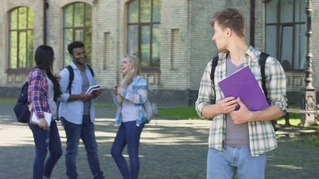 ethic : Lonely male student looking at happy laughing classmates standing near college