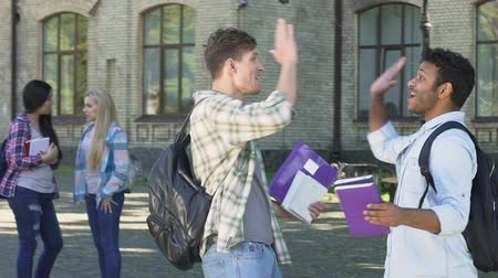 akadémia : Cheerful multiethnic male students rejoicing successful test passing, slowmotion