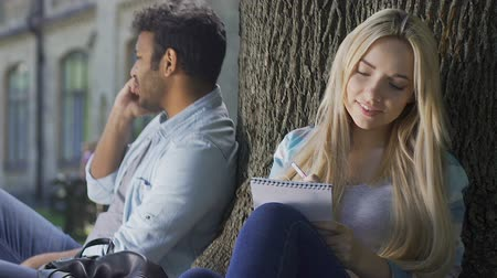 indifference : Guy talking on phone, his girlfriend composing love message for him, youth Stock Footage