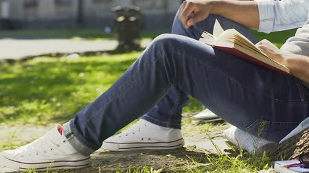 breathing fresh air : Teenager enthusiastically reading book sitting outdoors and breathing fresh air Stock Footage