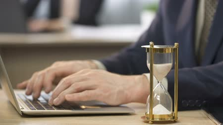 sandálias : Man in suit working on laptop at office, hourglass standing on the table, time Stock Footage