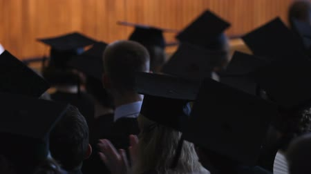 püskül : Students in black gowns and caps sitting at graduation ceremony, future