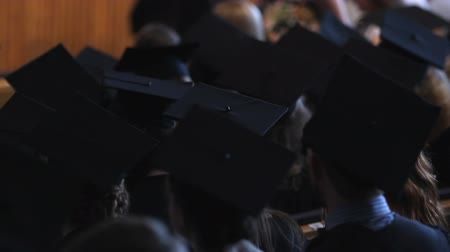 commencement : Group of students in academic dress waiting for graduation ceremony in hall Stock Footage