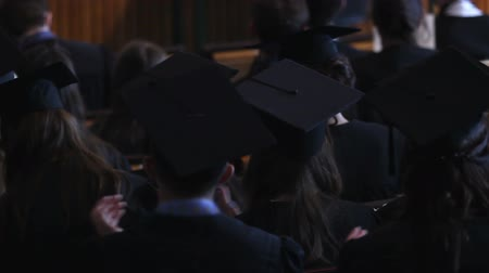 commencement : Girls and guys in black dresses and hats applauding at graduation ceremony Stock Footage