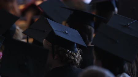 commencement : Young women in academic dresses watching graduation ceremony at university Stock Footage