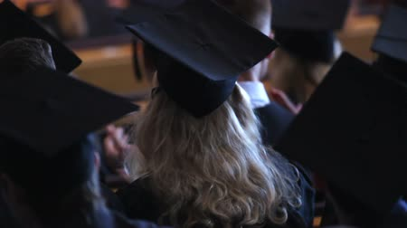 püskül : Excited blonde female in black dress and cap applauding teachers speech Stok Video