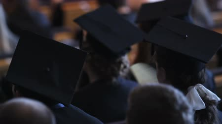 commencement : Tired students graduating from university campus, people sitting at hall Stock Footage