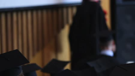 püskül : Girl in academic dress walking to stage to receive long-expected diploma