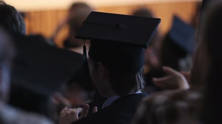 commencement : Excited alumnus in mortarboard applauding rectors speech at graduation ceremony Stock Footage