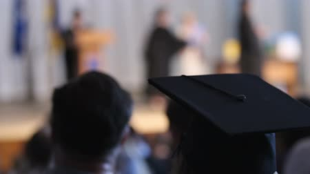 completion : Girl wearing mortarboard looking at stage and listening rectors congratulations