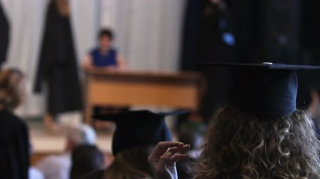 commencement : Happy students in hats and gowns watching graduation ceremony, receiving diploma Stock Footage