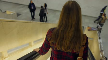zahmetsiz : Long-haired woman descending an escalator at shopping mall, free time, city life