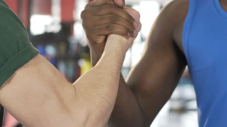 köszönt : Two male friends shaking hands in gym, muscular arms of strong men, support