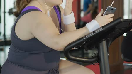lerdo : Sluggish bored lady spinning exercise bike pedal, playing on smartphone, lazy