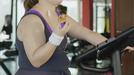 lerdo : Obese young woman with weak willpower eating donut during workout at gym