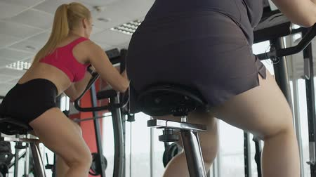 willpower : Girl with great willpower and motivation training leg muscles on stationary bike Stock Footage