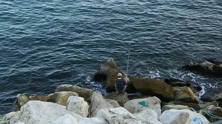 fishing pole : Fisherman sitting on huge stones and fishing, hobby and relaxation, recreation