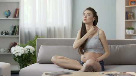 esneme : Future mother sitting on sofa and massaging neck and shoulders, tensed muscles