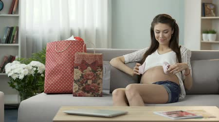 devanear : Mother-to-be taking baby shoes from shopping bag, putting on belly, baby girl Stock Footage