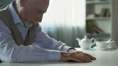 wistful : Depressed elderly man sitting at kitchen table, widower suffering loneliness Stock Footage