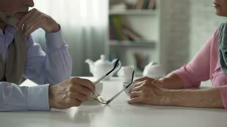 quarreling : Elderly couple sitting across table over cup of tea, tensed relationship, crisis Stock Footage