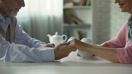 gentleness : Senior couple sitting at table with cup of tea, man taking woman hand, happiness