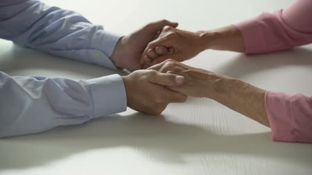 gentleness : Aged man and woman holding hands on table, mutual support and care, marriage