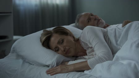 ból pleców : Retiree couple lying in bed awake, woman with her back to man, misunderstanding