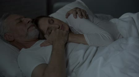 прижиматься : Elderly husband and wife sleeping in bed, woman put head on man chest, loving