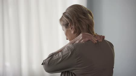 sudden : Elderly woman standing backwards, rubbing neck and shoulders, stiff muscles