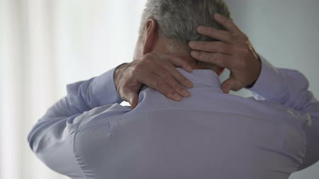 sudden : Male employee standing backwards, rubbing back of his neck, office desk worker