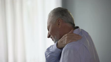плечи : Aged man standing sideways, touching neck in acute pain, trying to move head