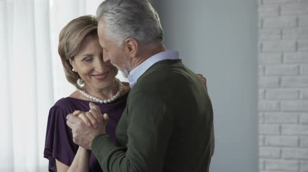 whispering : Senior couple dancing, man whispering to woman ear, romantic relationship, date Stock Footage