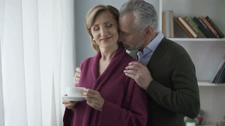gentleness : Senior woman standing with cup of tea by window, man hugging her from behind