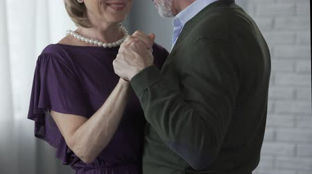 gently : Old male and female dancing, man kissing woman hand, stroking one another gently