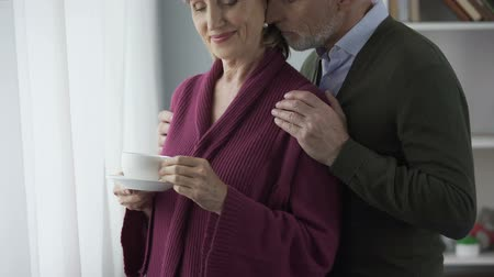 from behind : Elderly female with cup of tea by window, man hugging behind, kissing on cheek