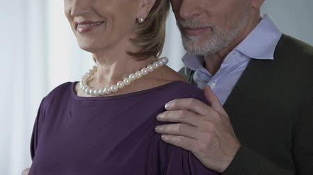 восхитительный : Elderly male kissing female in pearls on shoulder, special occasion, happiness Стоковые видеозаписи