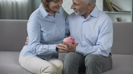 pago : Retired couple on couch holding piggy bank, matured paid out insurance, secure Stock Footage