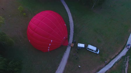 обязательство : Hot air balloon envelope getting inflated on ground, people walking around, fest Стоковые видеозаписи