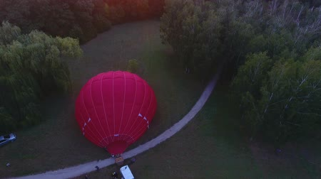 getting ready : Workers inflating hot air balloon envelope on ground, sun rising on horizon Stock Footage
