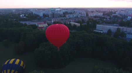 dirigível : Red hot air balloon floating over city green area at dawn, festival early flight Vídeos