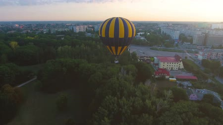fardo : Hot air balloon floating over city green area in morning, escape from routine