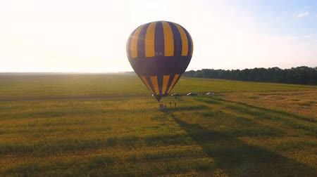 dirigível : People walking around wicker basket of air balloon landed in field, destination