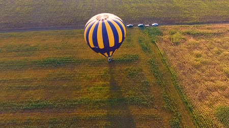 contestant : Basket of hot air balloon standing on field, people jumping from gondola, finish