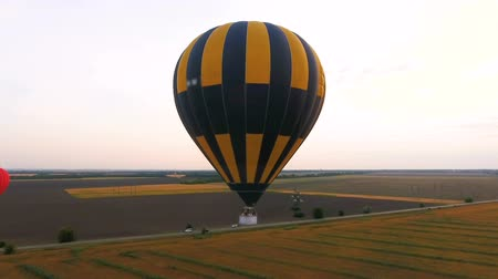 industrialization : Few hot air balloons flying over fields, road running amidst, industrialization Stock Footage