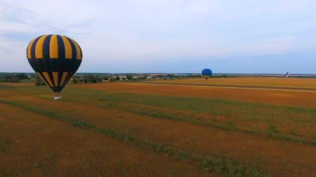 impressive skyline : Air balloons floating low over fields, village at background, agricultural power